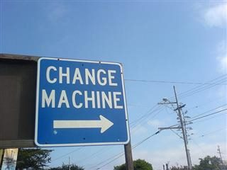 "Blue sign with white lettering that says, ""Change Machine"" with an arrow underneath the letters pointing to the right."