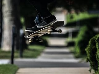 skateboarder  doing an ollie, feet and board only parts visible, up in the air