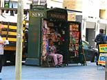a man sits in his newsstand on the street.