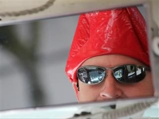 A mirror reflection of a man wearing sunglasses and a red hat.