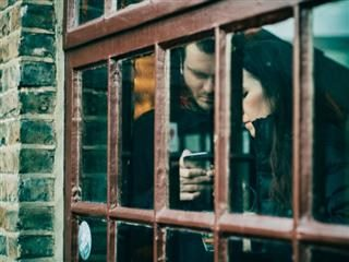 two people using a phone behind a window in a brick wall