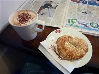 bagel and a cappuccino next to a newspaper on a table