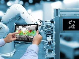 Man hand holding tablet with Augmented reality screen software and blue tone of automate wireless Robot arm in smart factory background
