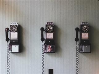 3 vintage rotary phones lined up on the wall