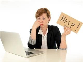 "A CIO at her desk with a laptop on it. The woman looks upset and is holding a sign that says ""help."""