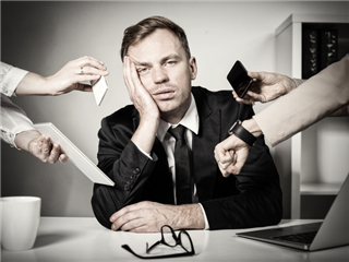 Businessman feeling overwhelmed at work, with several varying hands holding different (technologies, phone, digital watch, tablet, etc.) in his face.