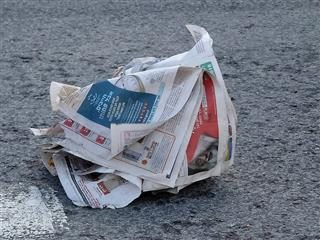 newspaper blowing in the wind on the ground