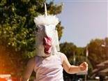 person walking down the street wearing a unicorn mask