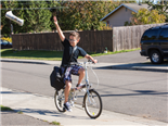 A newspaper delivery boy on a bike, throwing a newsletter into a driveway - Newsbyte concept