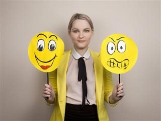 woman holding up happy and sad faces