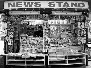 An outside news stand in black-and-white.