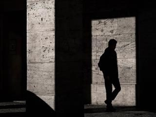 man standing in the shadows