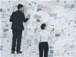 Two Businessmen working hard to pin data on a wall. - Data Management Concept