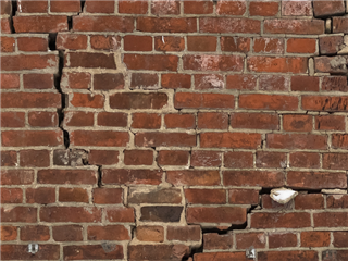 A cracked brick wall - cracks in infrastructure concept