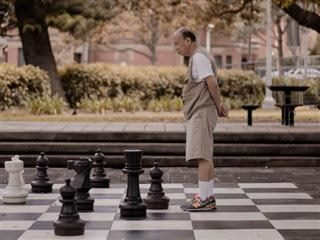 man standing in the middle of a very large chess board, studying the pieces