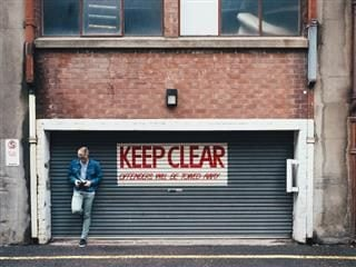 "man staring at phone, leaning against roller gate with sign ""Keep Clear"""