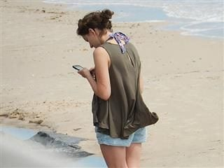 woman with cell phone on beach