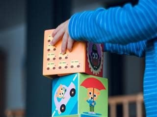 child stacking up building blocks