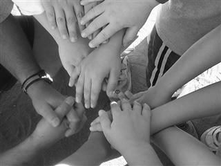 A black and white photograph of children's hands together in a huddle.