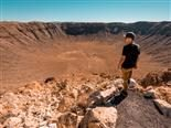 A man in the desert looking out over a giant meteors impact crater