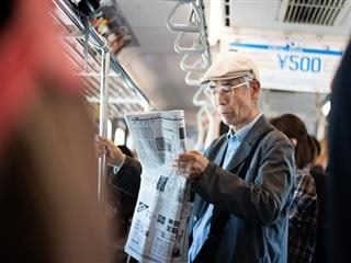 straphanger reading a paper