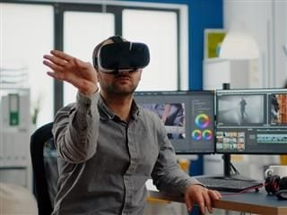 A man wearing a virtual reality headset sitting down and point to the right with his right hand.