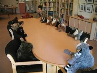 stuffed animals and one girl sitting around a table as if meeting