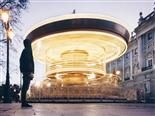 man viewing  a quickly spinning carousel