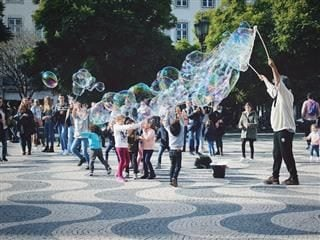children in a plaza playing with  very large bubbles