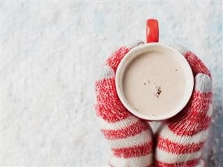 close up of someone's hands   in mittens, holding a cup of hot chocolate