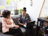 two women sitting on a couch collaborating on a laptop