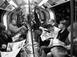 people reading newspapers on the subway