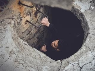 man climbing up out of a tunnel