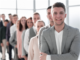 A businessman standing in front of a line of diverse young people, in an office lobby