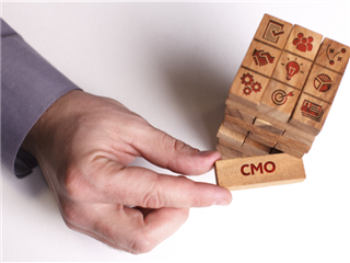 A man's hand removing a Jenga game piece from the structure. The piece of wood says CMO on it. The top of the Jenga pile has several icons representing skills