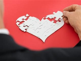 A businessman putting together a puzzle in the shape of a heart