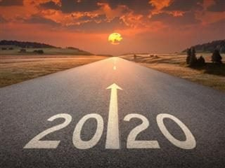 An illustration of 2020 written on the road of an empty highway at sunset.