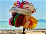 vendor standing on sunny beach with a number of flotation devices for sale