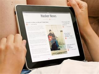 person reading a Flipboard magazine on a tablet