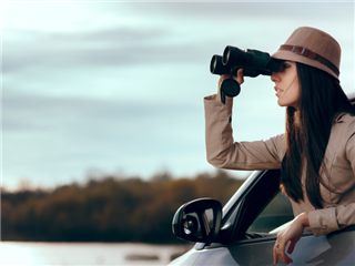 A female private investigator, hanging out a car window, looking through binoculars for evidence