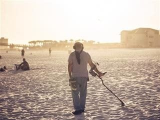 man with a metal detector at  the beach