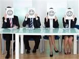 Four business executives sitting across a table holding up a piece of paper with a smiley face on it over their faces.