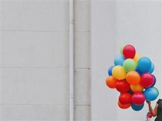 woman's arm holding a large group of brightly colored balloons