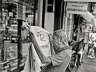 Man sitting down reading a newspaper.