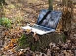 computer on a tree stump in a field