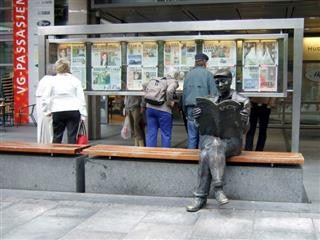 Statue of a man sitting down, legs crossed, reading a newspaper, in front of people looking into a glass case full of newspapers.