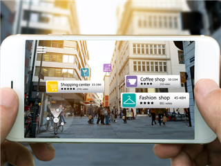 A hand holding a smartphone using an AR application to check out relevant information about the spaces around the customer. City background