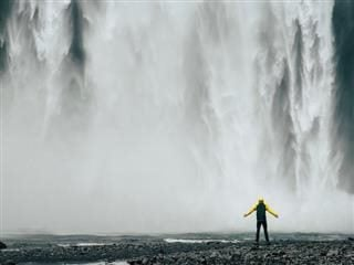 person standing in front of waterfall with arms spread