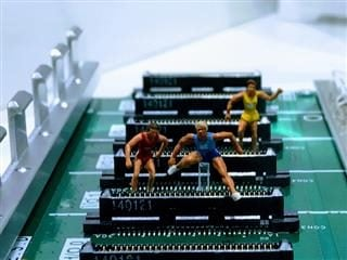 toy figures jumping over parts of a computer board