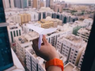 paper airplane over a city